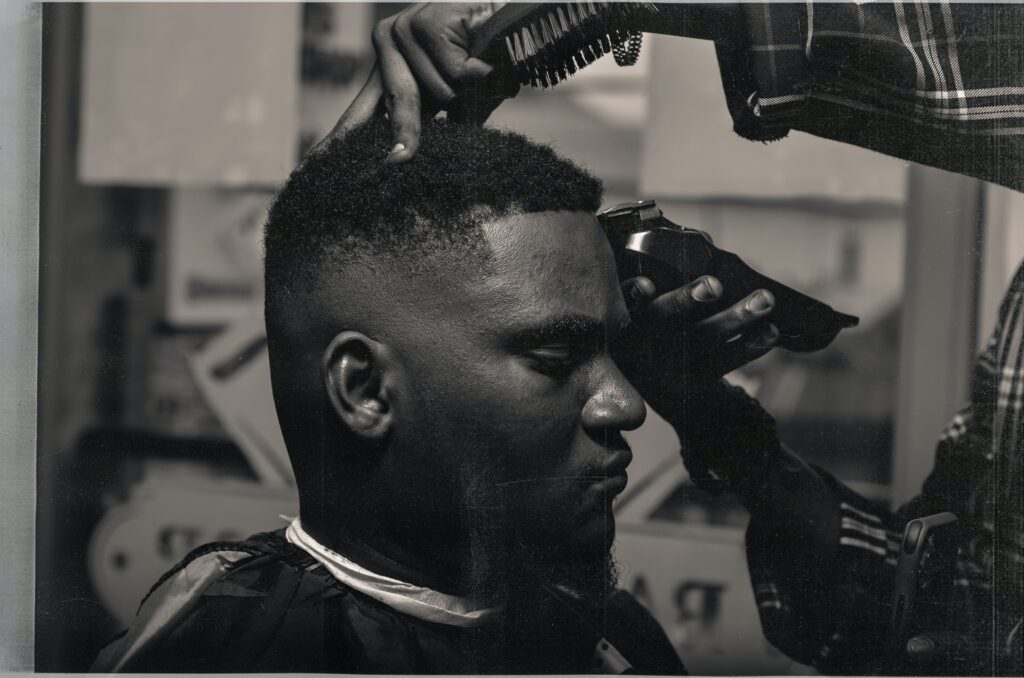 Black and white image of a black man getting a haircut at a barbershop. Credit: BariKive from Pexels.