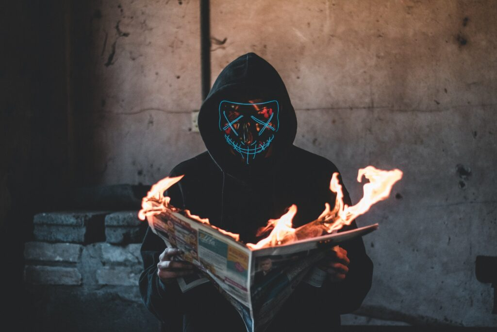 Man with LED mask reading a burning newspaper. Photo by Connor Danylenko from Pexels.