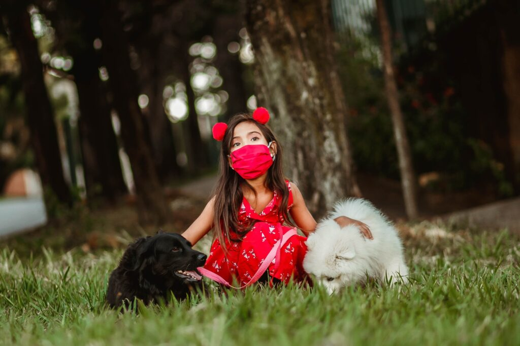 Girl in a park, wearing mask with two pet dogs. Photo by Helena Lopes from Pexels