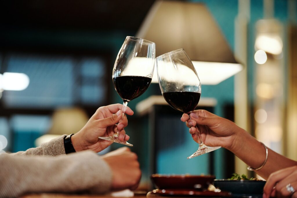 Two people clinking wine glasses together. Photo by Jep Gambardella from Pexels