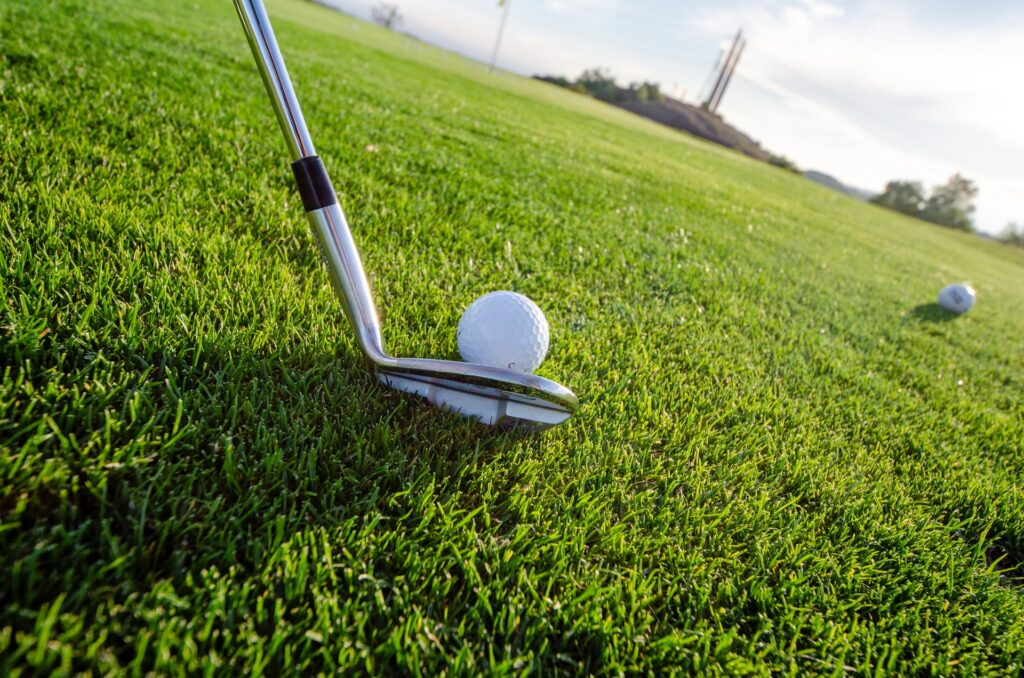 Putter and golf balls on golf course. Photo by Robert Ruggiero on Unsplash.