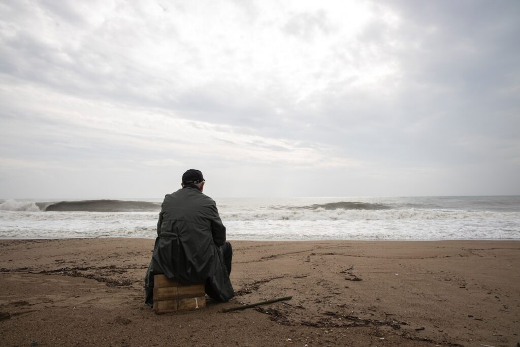 Older man sitting alone on beach. Photo by Engin Akyurt from Pexels